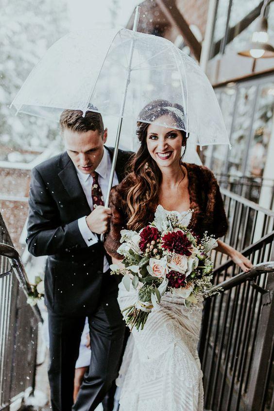 Soluzione per il matrimonio in caso di pioggia: sposo copre la sposa con ombrello