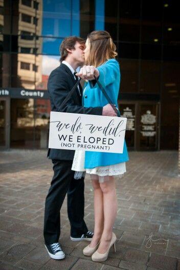 Elopement: sposi che si baciano e tengono un cartello in cui dichiarano il matrimonio in solitaria