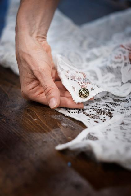 Bianca Collezione Milano mano che fa vedere bottone su dettaglio abito in pizzo