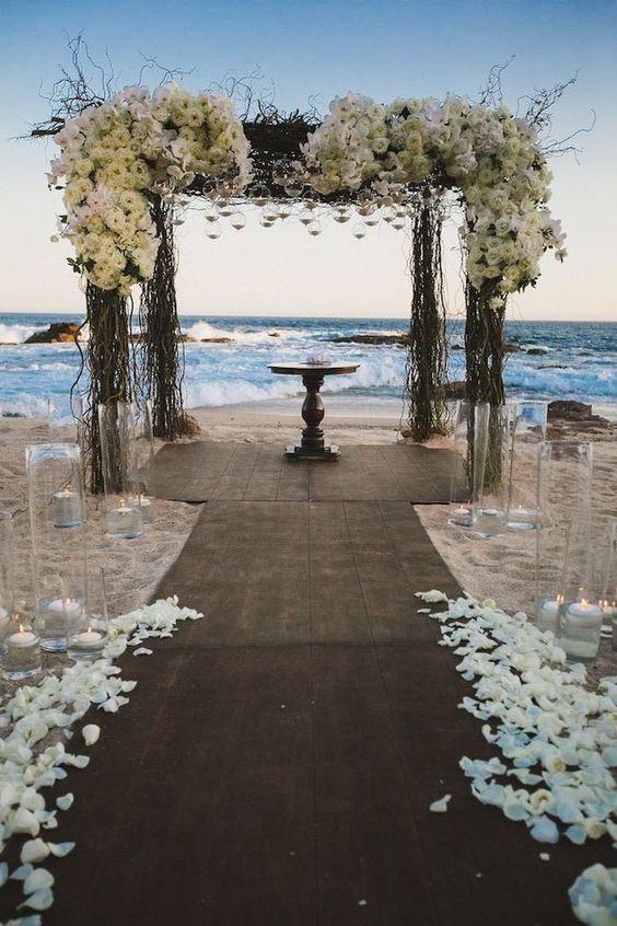 Matrimonio all'aperto: arco di rami secchi e fiori bianchi in riva al mare