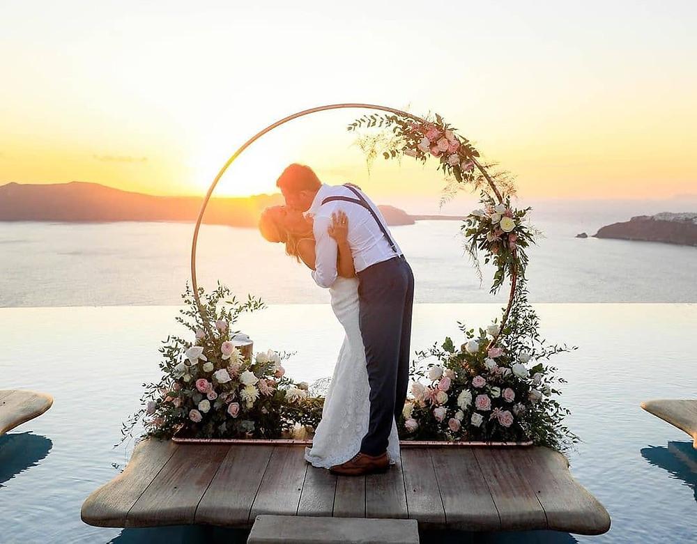 matrimonio a santorini sposi che si baciano al tramonto sotto arco di fiori