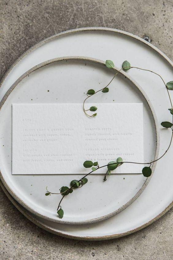 Matrimonio in stile minimal chic: mise en place con menu su cartoncino bianco e foglie di eucalipto