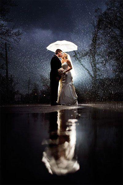 Soluzione per il matrimonio in caso di pioggia: sposi in posa sotto la pioggia e luce della luna