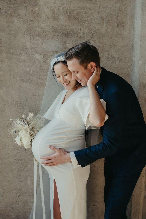 sposa incinta con dietro il marito