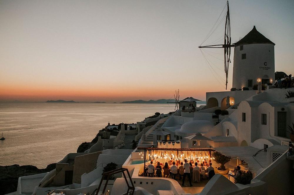 terrazza al tramonto ad oia, santorini, con mulino al vento