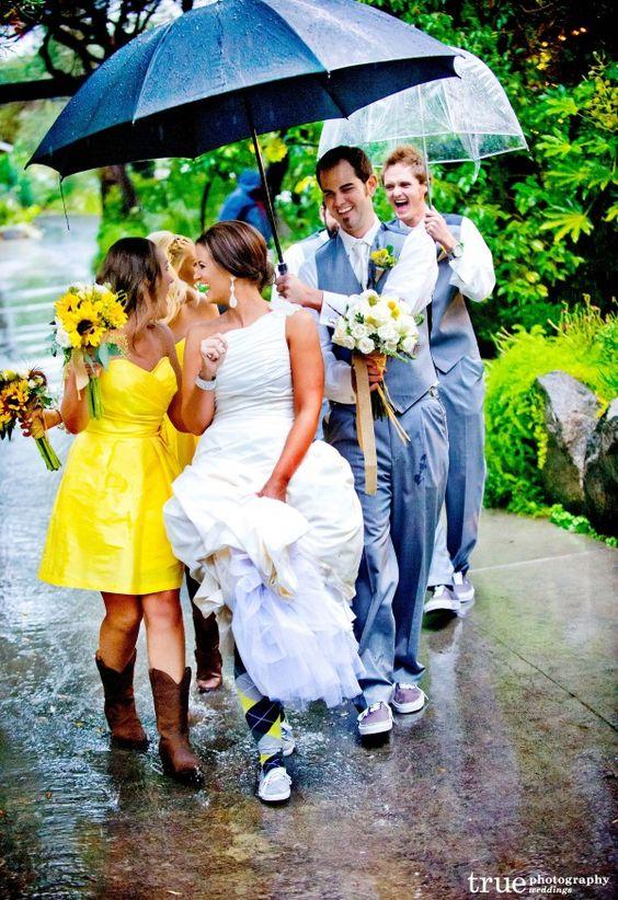 Soluzione per il matrimonio in caso di pioggia: sposa e damigella vestita di giallo sotto la pioggia