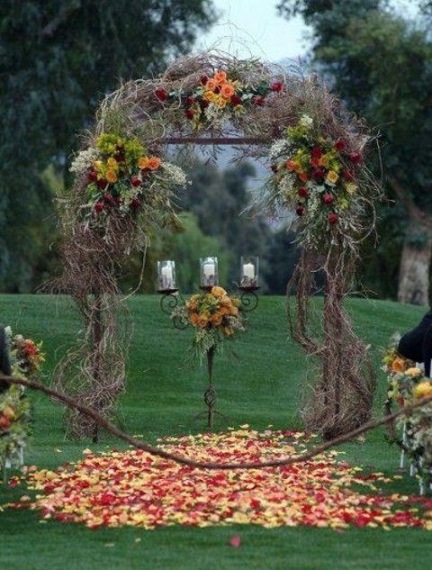 Matrimonio all'aperto: arco di fiori e rami secchi in un giardino
