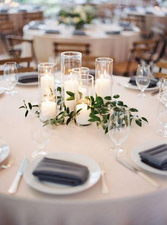 Matrimonio in stile minimal chic: centro tavola con candele bianche e foglie d'ulivo
