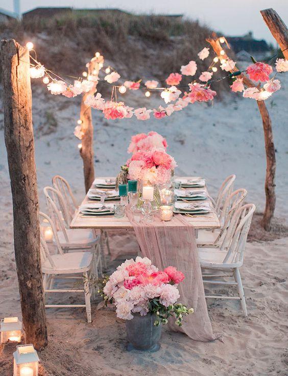 Matrimonio all'aperto: tavolo di legno con fiori color corallo e lucine calde