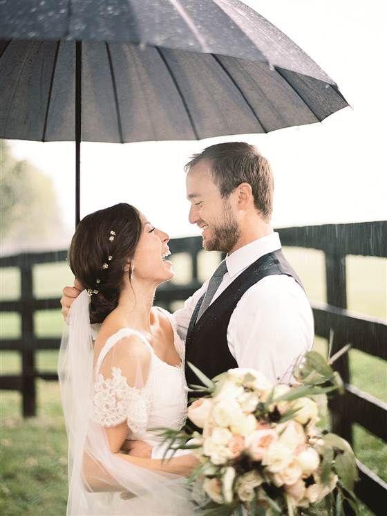 Soluzione per il matrimonio in caso di pioggia: sposi sorridenti sotto la pioggia ed ombrello
