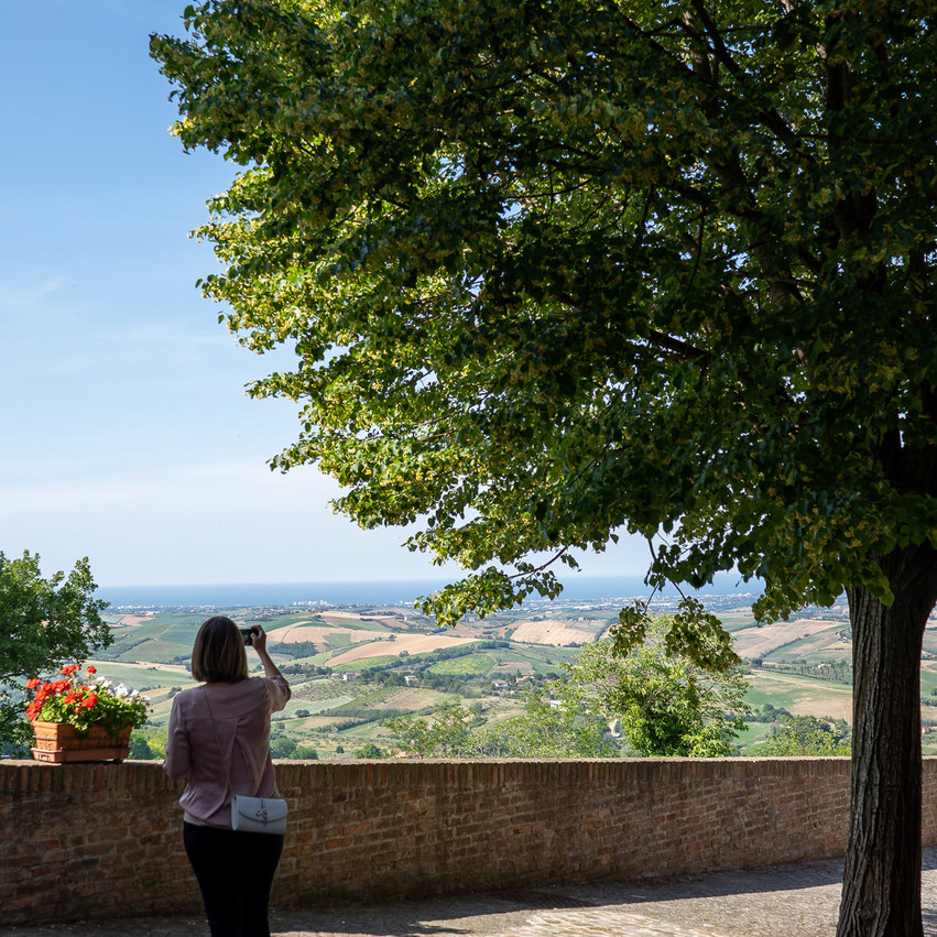 Montegridolfo Donna vista di spalle che fa una foto sulla vallata