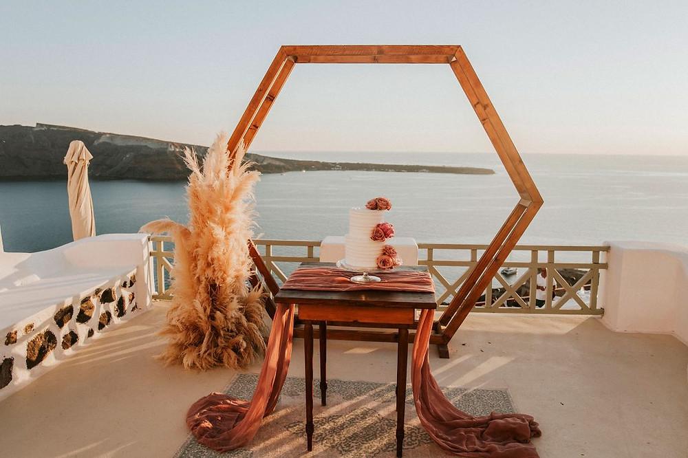 terrazza di Santorini al primo calar del sole, background di legno, pampas e torta bianca