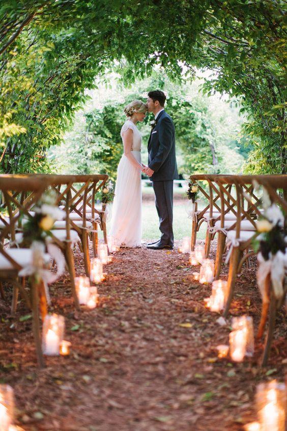 Matrimonio all'aperto: 2 sposi si baciano sotto un arco verde in un bosco