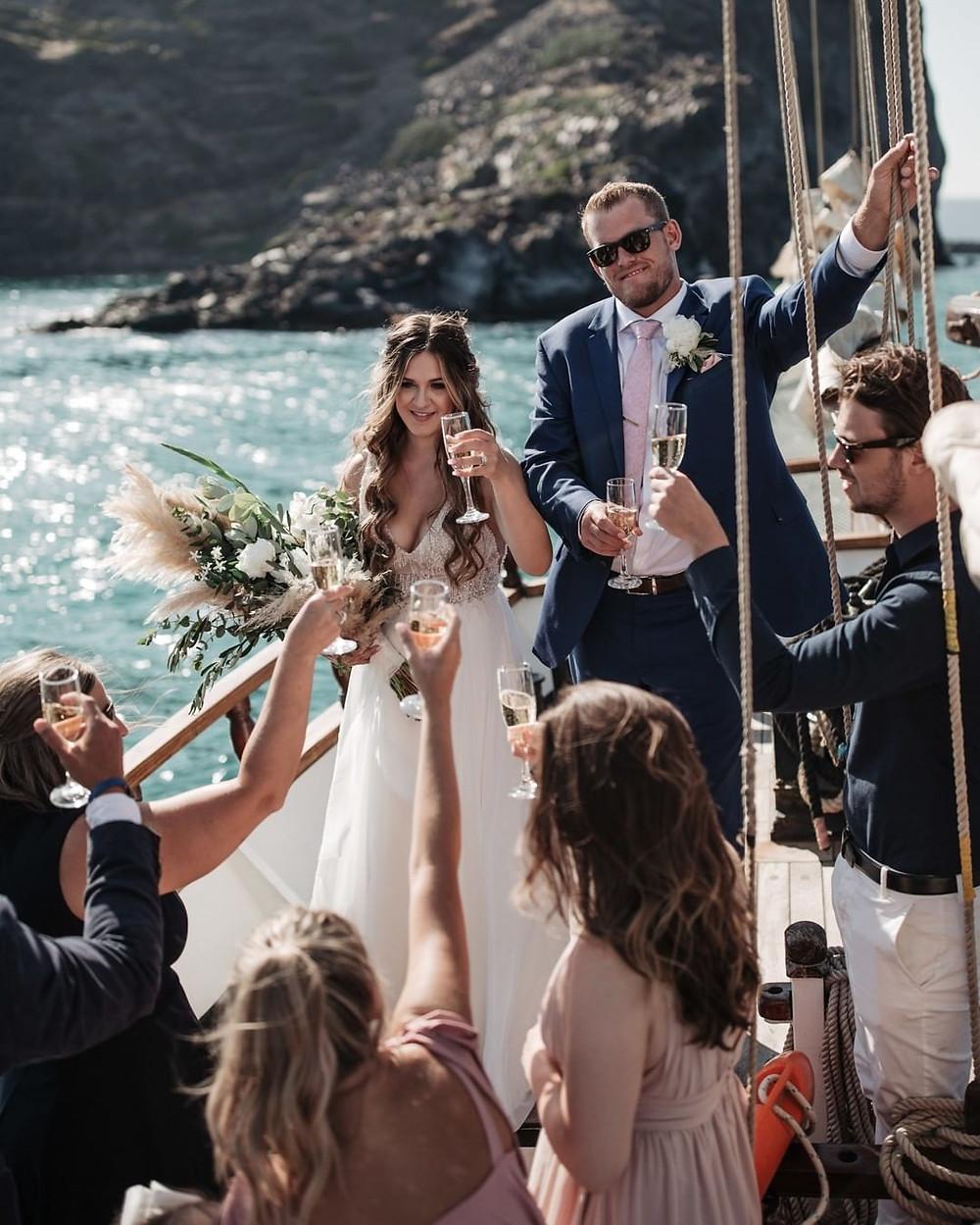matrimonio a santorini sposi e ospiti che brindano su un veliero