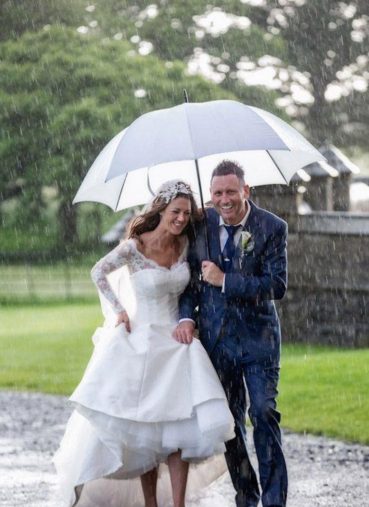 Soluzione per il matrimonio in caso di pioggia: sposi con ombrello bianco