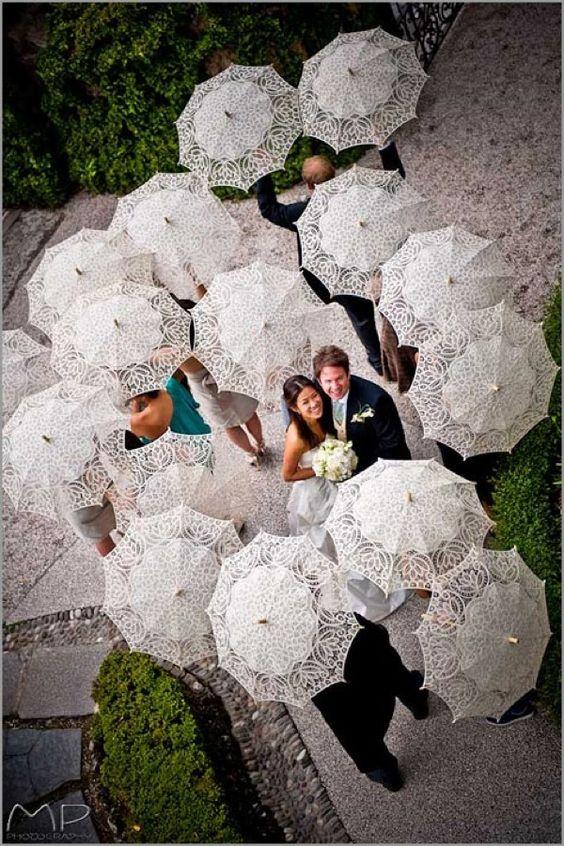 Soluzione per il matrimonio in caso di pioggia: sposi circondati dagli ospiti tutti con ombrello bianco a parte loro