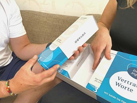 Ein Paar testet die Date Night Vertraute Worte und öffnet eine der Schachteln der Geschenkbox