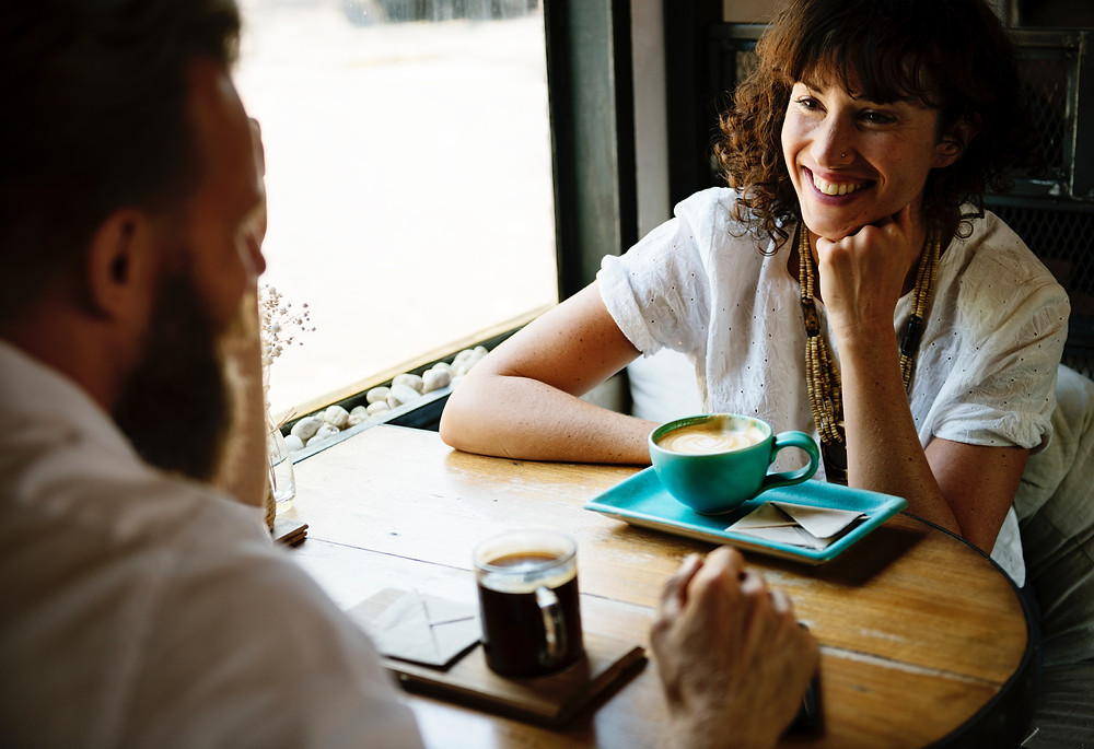 man and woman having coffee on wooden table
