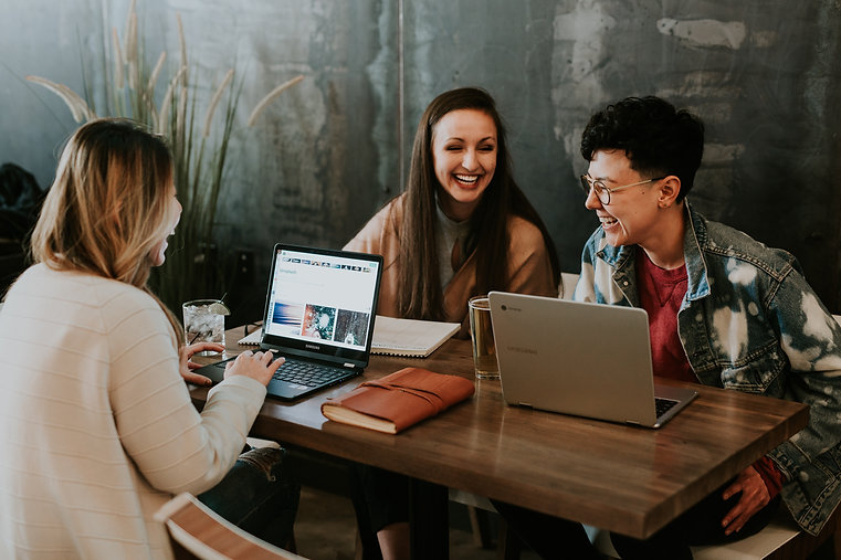 3 women talking at table with computers