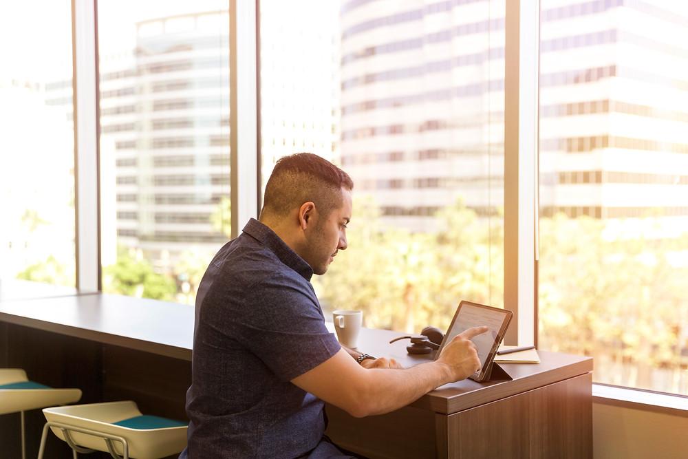 man writing his linkedin profile at a table