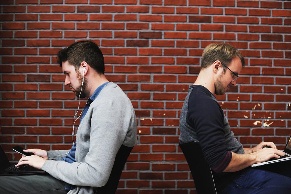 2 men sitting back to back