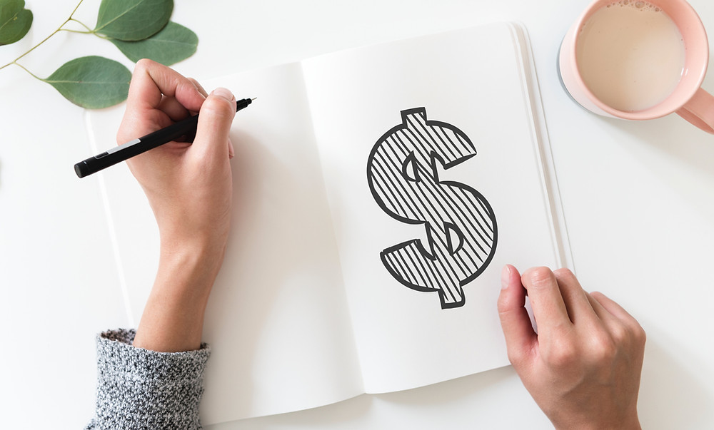 woman drawing a dollar sign in notebook