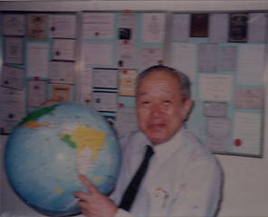 J. Wada, holding a world globe in his office in Tokyo 1989, talking about creating a big society worldwide