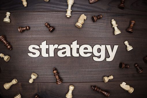 The word strategy on wooden background with scattered chess pieces
