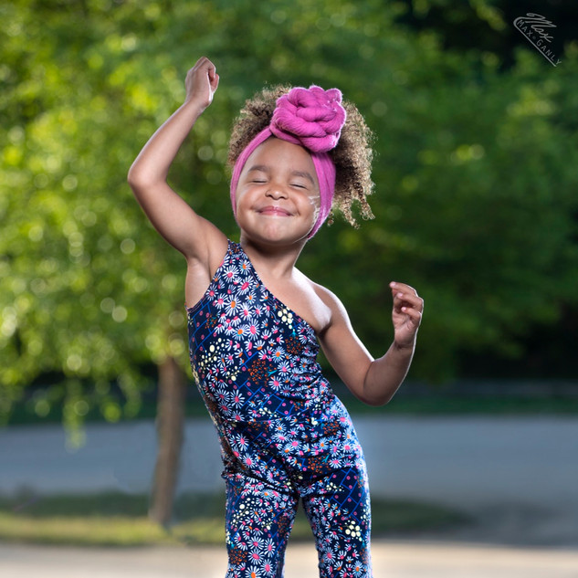 African american toddler with fun hair bow doing dance move