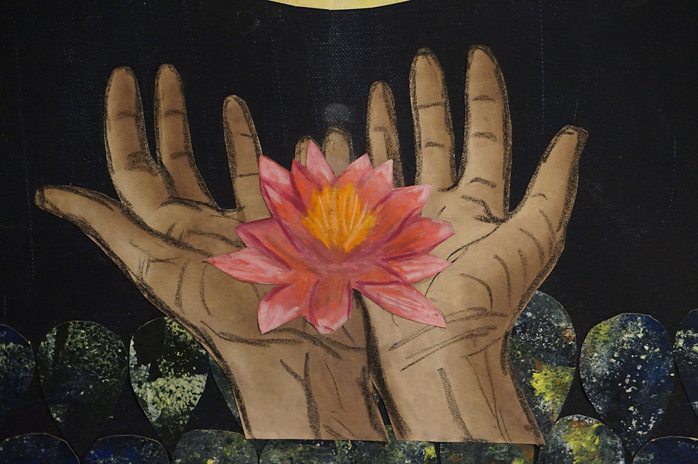Hands open with a lotus flower