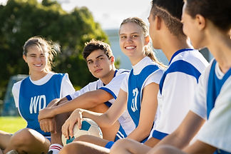 happy-smiling-young-football-players-sit