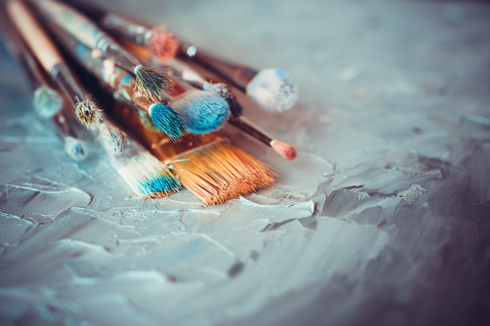 Dirty paint brushes sitting on table