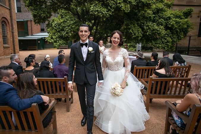 Walking back up the ailse after wedding ceremony at Hyde Park Barracks, Sydney. Photography by best wedding photographer sydney, Grant Hoskinson Photography.