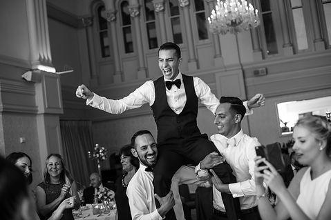 Groom being lifted. Wedding reception. QVB Tea Room. Wedding photgraphy by Sydney wedding photographer Grant Hoskinson Photography.