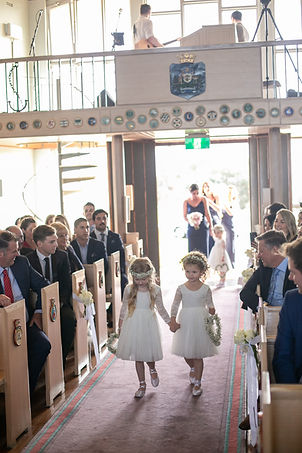 Flower girls walking down the aisle at the wedding ceremony at HMAS Watson Chapel. Wedding photography by best Sydney wedding photographer, Grant Hoskinson Photography.