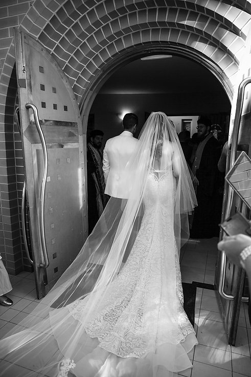 Bride and groom enter the church. St Mary and St Merkorious Coptic Orthodox church. Photography by best Sydney wedding photographer Grant Hoskinson Photography.