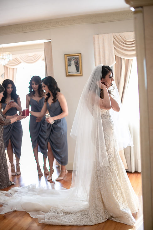 Bride putting on her wedding earrings. Photography by best Sydney wedding photographer Grant Hoskinson Photography.