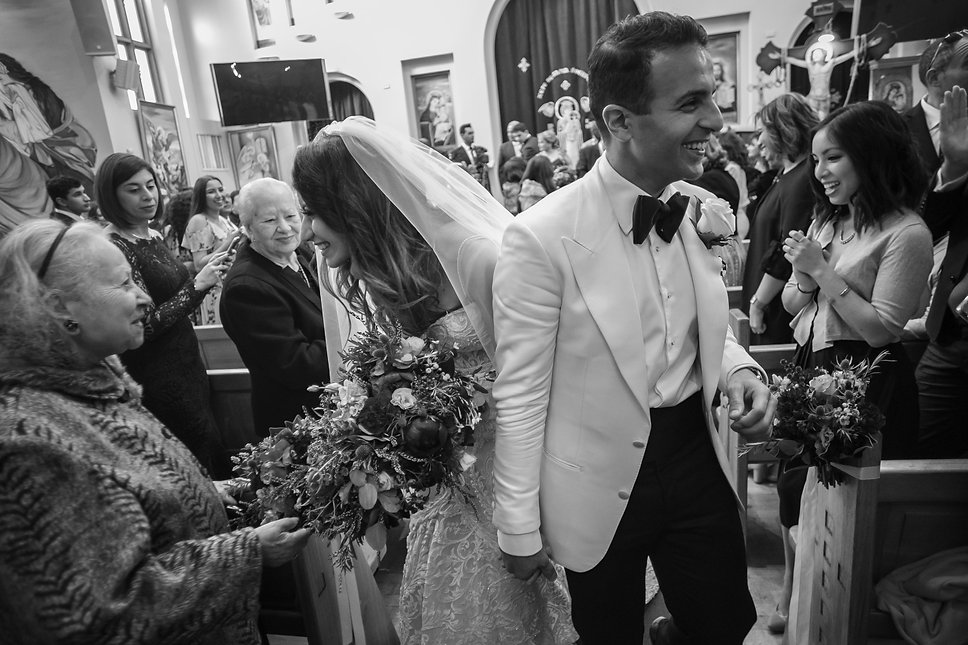 Bride and groom walking back up the aisle after the wedding ceremony. Bride and groom during Egyptian Coptic wedding ceremony. St Mary and St Merkorious Coptic Orthodox church. Photography by best Sydney wedding photographer Grant Hoskinson Photography.