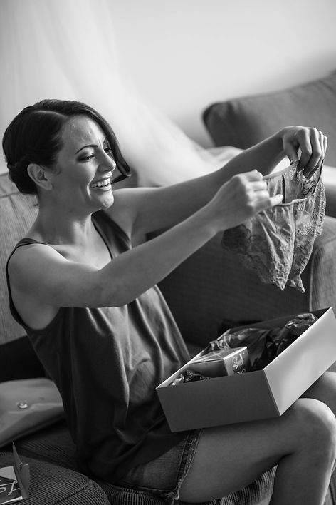 Beautiful wedding photography by popular wedding photographer, Grant Hoskinson Photography. Bride opening present from groom.