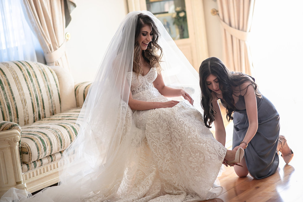 Bridesmaid helping bride to put on her wedding shoes. Photography by best Sydney wedding photographer Grant Hoskinson Photography.