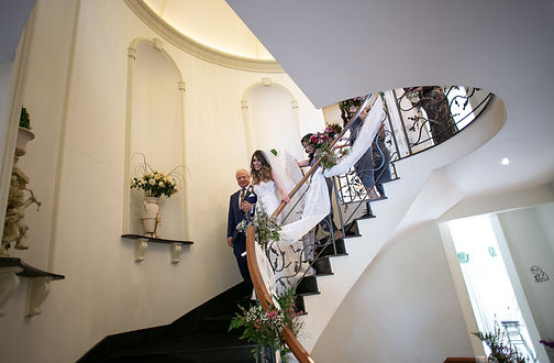 Father of the bride escorting the bride down the stairs after putting the dress on. Photography by best Sydney wedding photographer Grant Hoskinson Photography.