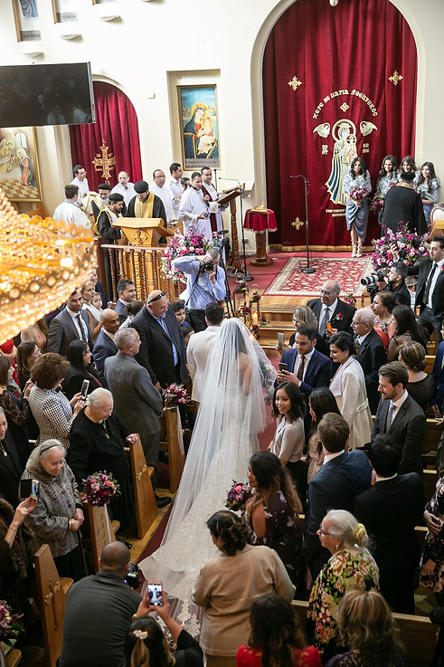 Bride and groom walk down the aisle to start the wedding ceremony.St Mary and St Merkorious Coptic Orthodox church. Photography by best Sydney wedding photographer Grant Hoskinson Photography.