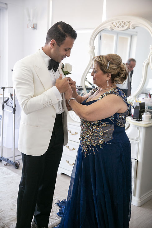 Mother of the groom putting on the buttonhole flower. Photography by best Sydney wedding photographer Grant Hoskinson Photography.
