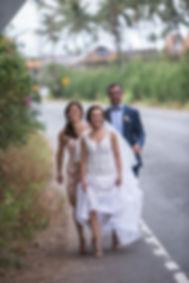 Bride walking on road.