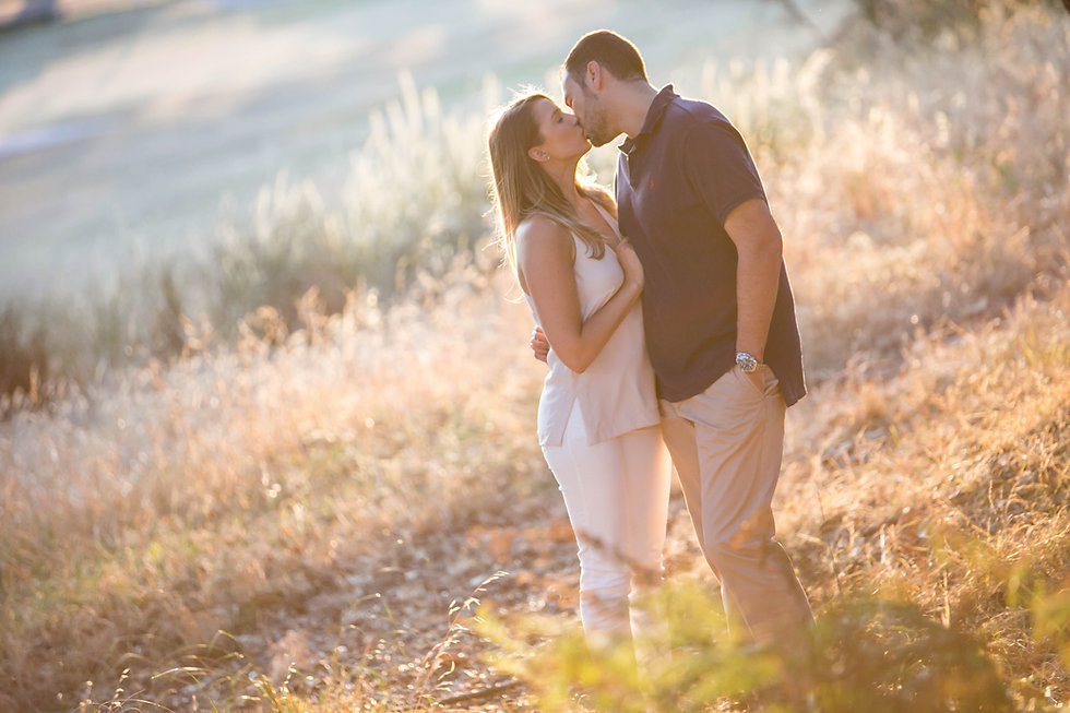 young couple kissing in the park with beautiful light on their engagement shoot. Engagement photos. Pre wedding shoot.