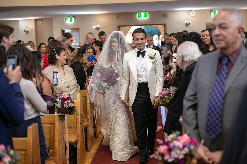 Bride and groom walking down the aisle to start the wedding ceremony. St Mary and St Merkorious Coptic Orthodox church. Photography by best Sydney wedding photographer Grant Hoskinson Photography.