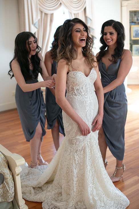 Bride putting her wedding dress on helped by the bridesmaids. Photography by best Sydney wedding photographer Grant Hoskinson Photography.