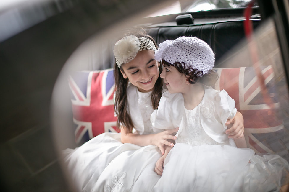 Flower girls in the back of the wedding car. Wedding photography by best sydney wedding photographer, Grant Hoskinson Photography.