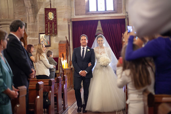 Bride and father of the bride walking down the aisle at the Cathedral of the Annunciation of Our Lady Greek church, Redfern, Sydney. Wedding photography by best sydney wedding photographer, Grant Hoskinson Photography.