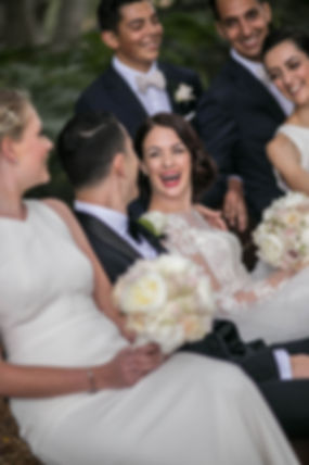Bride laughing with the bridal party in Hyde Park, Sydney. Wedding photgraphy by Sydney wedding photographer Grant Hoskinson Photography.